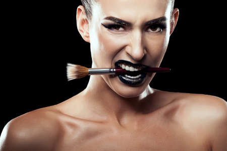 aggresive: Woman with make up brush in mouth over black background. Aggression. Aggresive expresion. Studio shooting. Concept fashion style. Make up concept Stock Photo