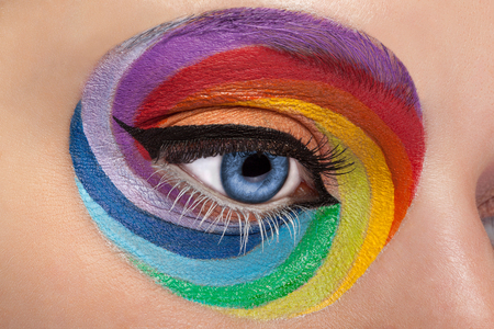 stage make up: Close up blue eye with artistic rainbow make up. Colors and colorful. Joy. Artistic and fashion make up. Make up addiction. Cosmetics. On stage make up
