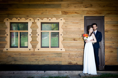 wedding photography: Bride and groom in front of house holding togher. Happy familly. Wedding. Wedding photography. Weddin photo