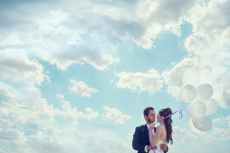 happines: Just married bride and groom with baloons in hand over cloudy sky. Emotions and love. Happines and joy Stock Photo
