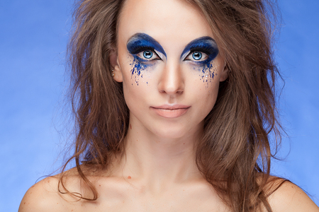 stage make up: Girl with fantasy blue make up ove blue background. Blue eyes. On stage make up