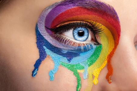 Vloeiende kleuren op een oog in de mode stadium make-up. Regenboog van kleuren spectrum. Blauw oog. Close-up details. Macro-opnamen. Mode op het podium maken. Levendige kleuren
