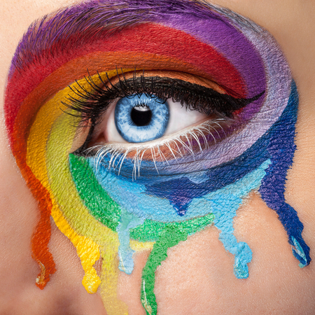 stage make up: Flowing colors on an eye in fashion stage make up. Rainbow of color spectrum. Blue eye. Close up details. Macro shooting. Fashion on stage make up. Vibrant colors Stock Photo