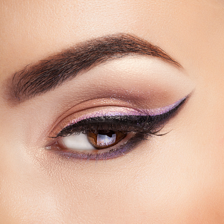 Eye with professional make up on it in close shooting. Studio lighting. Beauty and fashion. Make up and cosmetics. Cosmetic and make up advertising Фото со стока