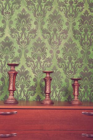 rococo: Three vintage chandeliers on green rococo style pattern background. Rich interior. Vintage toning