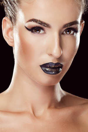 stage make up: Woman with black make up and black lips on black background. Studio shooting. Beauty and fashion. Make up addiction. On stage make up. Stock Photo