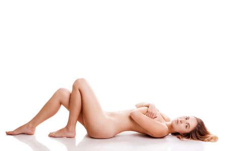 nackt: Nackte Frau auf dem Boden isoliert �ber wei�e backgorund in Studioaufnahmen liegen. Erotik und Sinnlichkeit. Sex und Begierde. Gesunde schlanke nackte K�rper