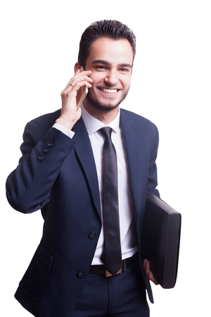 employe: Happy businessman in suit smiling while talking on the phone with a folder in hand isolated over white background in studio photo. Successful business and happy employe