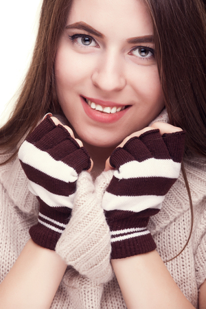 fingerless gloves: Pretty girl smiling with fingereless gloves on hand in studio photo. Winter emotions. Happy woman getting cozy Stock Photo