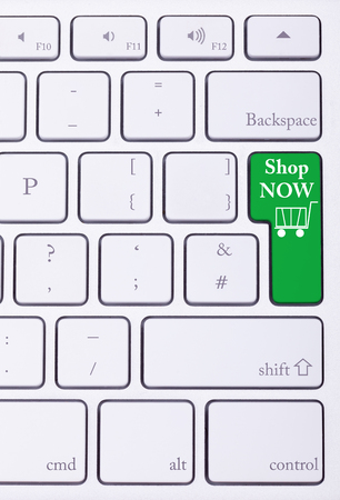 consumerism: Shop now green key on aluminium keyboard. Sale and online shoping. Consumerism Stock Photo