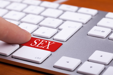 adult sex: Finger pressing on red button with sex word on it. Sex and xxx sites. Adult content only