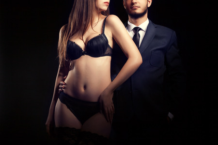 sensual sex: Woman in underwear next to man in suit on black background in studio shooting. Sexuality and fetish. Luxury erotic games