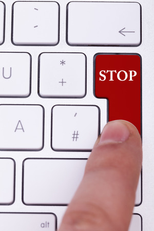 end user: Finger pressing a red stop button on keyboard. Stopping a process