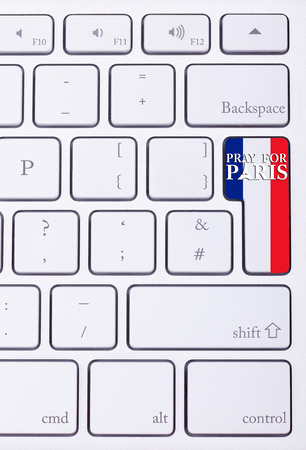 atack: Pray for Paris sign on france flag in keyboard. International suport for Paris victims in terrorist atack