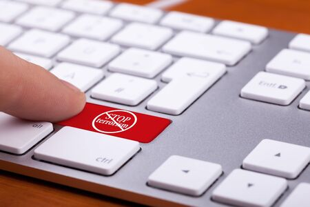 victim war: Finger pressing on red button with stop terrorism word and sign on it. Stop the war and the violence against free people. Conceptual Stock Photo