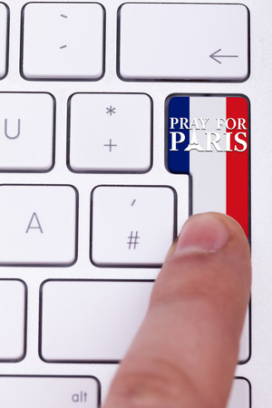 terrorist attack: Pressing pray for Paris sign on key with France flag. Terrorist attack against France. International suport for terrorist victims in Paris atack