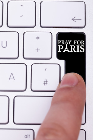 terrorist: Pressing black button with pray for paris text and sign. Terrorist attack against France