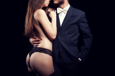 sex activity: Gorgeous woman in underwear next to men in classical suit on black background. Erotic studio photo. Concept of rich and power businessman Stock Photo