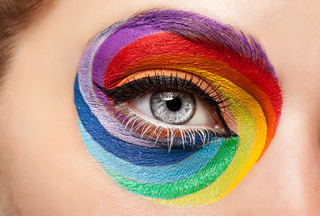 look make: Close up eye with fashion art on stahe make up. Fashion make up and excentric glamour concept. Rainbow make up
