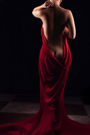 desnuda volver artístico de la mujer con cortinas rojas a su alrededor. Estudio de fotografía. Belleza y atractivo desnudo artístico