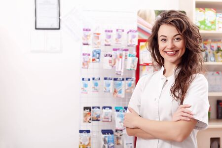 pharmaceutics: Smiling healthcare system worker in pharmacy posing at camera. Healthcare business. Pharmaceutics consultation Stock Photo