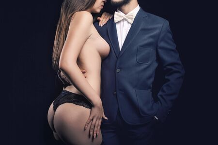 sex activity: Sensual woman in erotic pose next to rich men in business suit on black background in studio photo. Sexuality and erotica Stock Photo