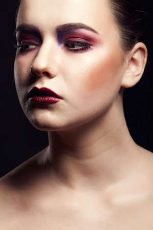 eye red: Portrait of beautiful girl with on stage make up and red lips on black background in studio photo. Professional make up. Deep shadows and artistic photo Stock Photo