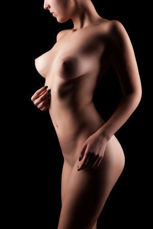 Naked woman with perfect body on black background in studio photo. Sensuality and art nude