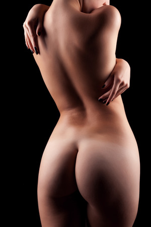 Naked woman with perfect body on black background in artistic image with deep shadows. Art nude. Sensuality and sexuality