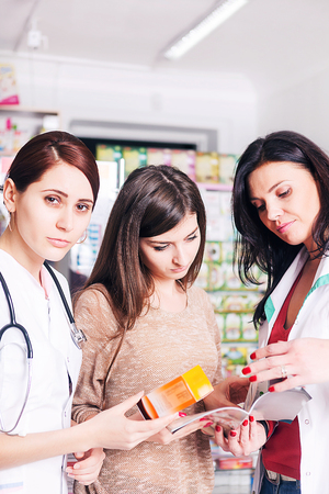 pharmaceutics: Two female doctors explaining a product to client inside a pharmacy. Healthcare buiness. Business. Healhtcare and client care. Pharmaceutics Stock Photo