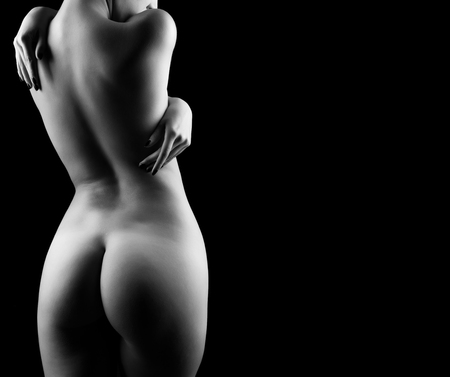 Naked woman in black and white with negative copyspace on black background in artistic image with deep shadows. Art nude Фото со стока