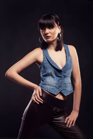 Woman model posing in leather pants and jeans jacket in studio. Fashion posing on black background