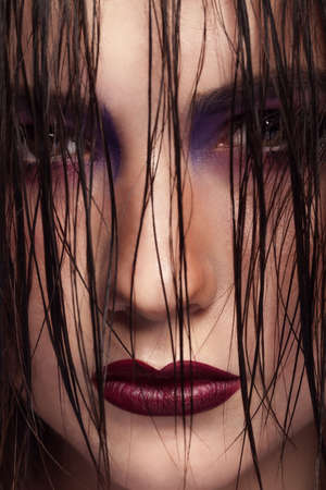 stage make up: Woman with wet hairs and scary look. Red lips and on stage fashion make up. Horror Stock Photo