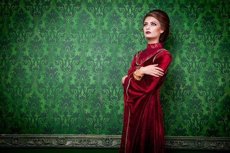 Woman in vintage clothes on green rococo wall. Vintage retro fashion. Beauty. Luxury interior