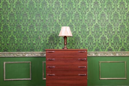 rococo: Vintage lamp on chimney on green retro pattern background. Rococo style