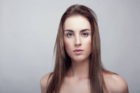 young adult woman: Woman with natural make up on grey background in studio photo