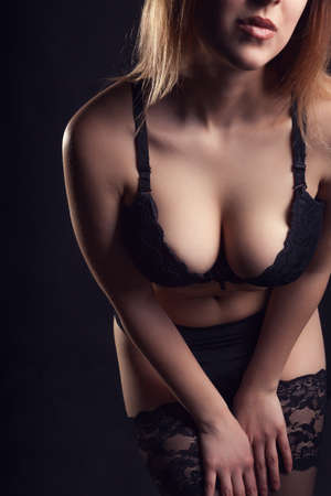 sensuality: Sexy woman with big breasts on black background in studio photo. Sexuality and sensuality. Beauty.