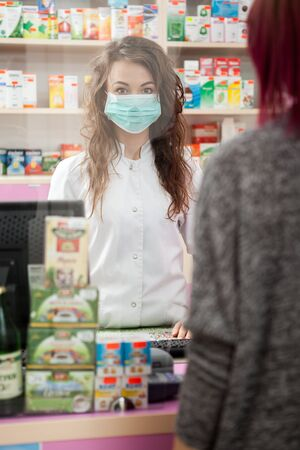 a lady doctor: Pharmacist and client with mask inside a pharmacy. Healthcare business