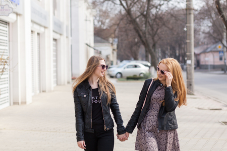 wheather: Two female friends enjoying a walk in sunny wheather outside. Lifestyle