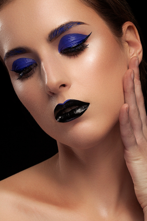 stage make up: Womam with fashion blue make up on black background in studio shooting. Extravagant make up. Colorful art stage make up with black lips Stock Photo