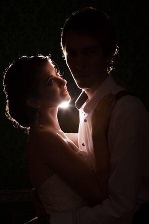 iluminado a contraluz: Novia que mira a su marido con una luz detrás. escenario de luz de fondo. Amor y Familly