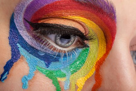 stage make up: Eye with sprayed colors in rainbow form in close up. Fashion on stage make up Stock Photo