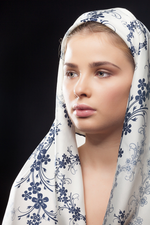 femininity: Girl with russian type scarf on black background. Femininity and purity. Beauty and fashion