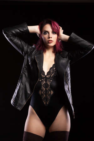 Sexy readhead in body lingerie and leather jacket looking sensual at the camera. Sexuality and sensuality Stock Photo