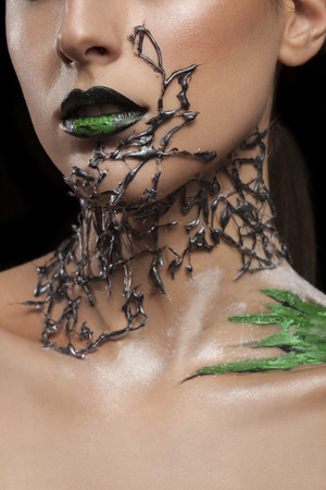 stage make up: Girl with black fashion mesh arround neck and green make up on black lips. Fashion on stage make up. Artistic make up. Studio
