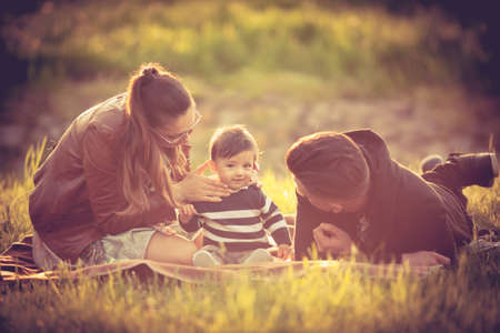 wheather: Happy familly with their kid in the park in sunny wheather