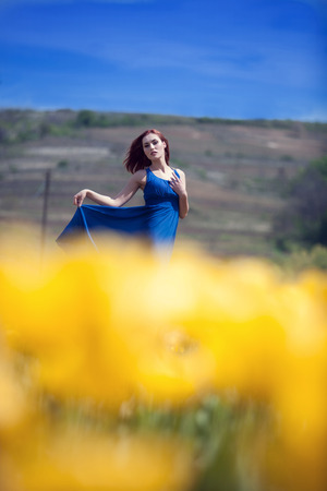 tulips field: Woman in yellow tulips field outside photo. Beauty and naturality Stock Photo