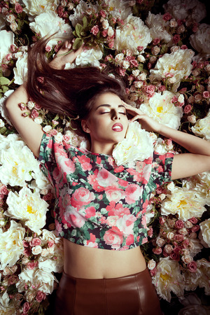 looking away from camera: Woman lying in flowers looking away from camera. Fashion and beauty. Fashion toning. Make up and concept