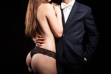 nackter junge: Luxus und Reichtum. Mann, der eine nackte Frau im Bikini neben ihm auf schwarzem Hintergrund im Studio. Erotica und Leidenschaft Lizenzfreie Bilder