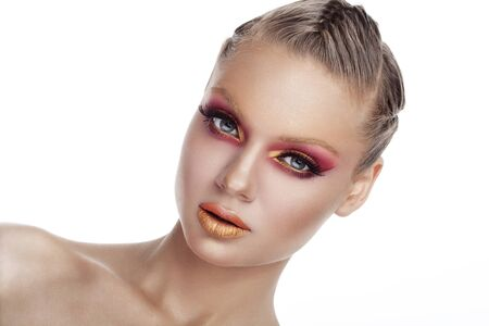 stage make up: Woman with red and gold art stage make up on white background in studio photo. Beauty and fashion. Art stage conceptul make up Stock Photo